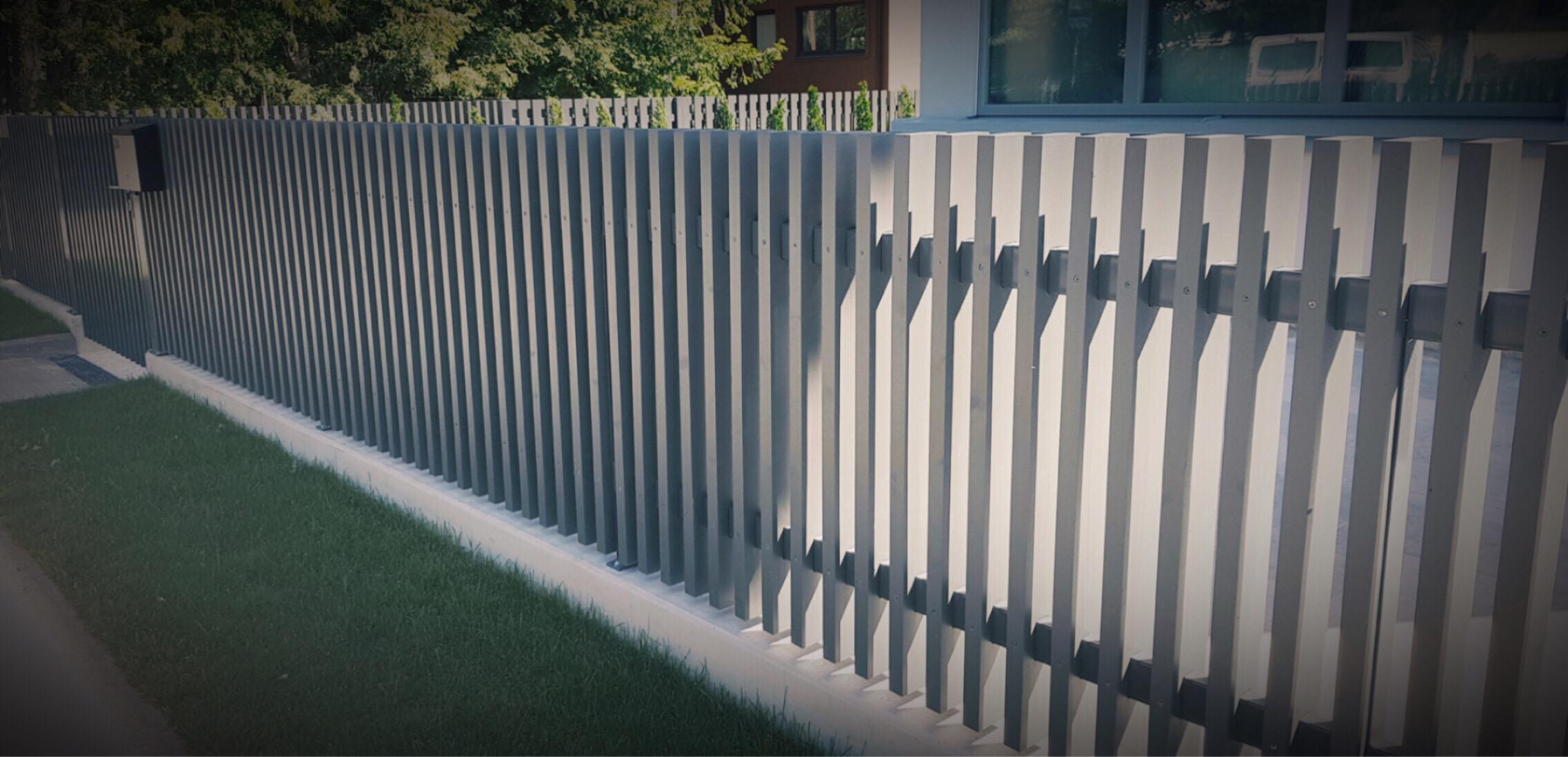 Puidust piirdeaed, metallpõõnad läbivad lippe